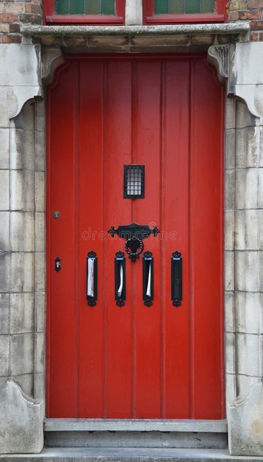 Старым дверь покрашенная красным цветом с почтовыми ящиками почты стоковое изображение