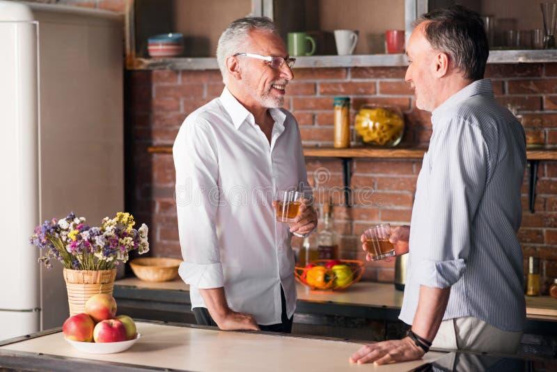 2 старых мужских друз имея пить в квартире стоковая фотография
