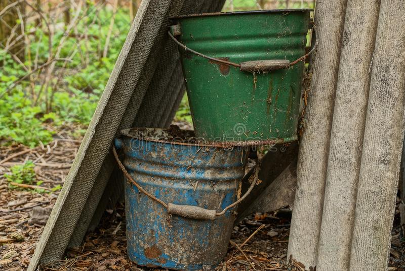 2 старых пакостных ведра в саде стоковое фото rf