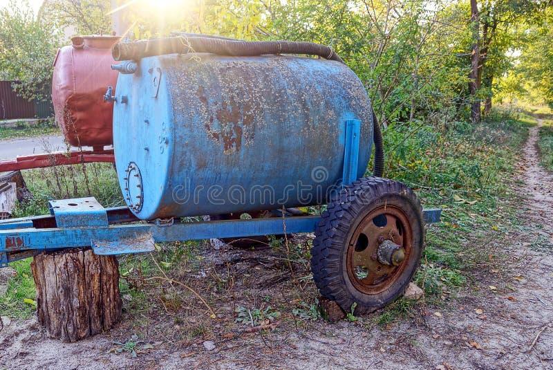 2 старых ржавых бочонка на колесах на улице стоковые фотографии rf