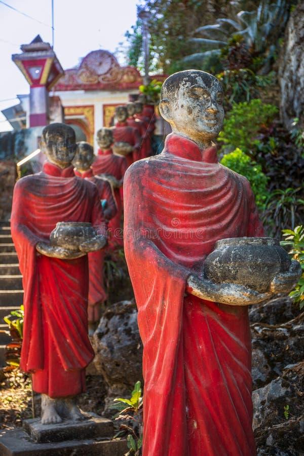 Статуи буддийских монахов каменные гребут на пещере Thaung Ka Kaw, Hpa-an, Мьянме стоковое фото rf