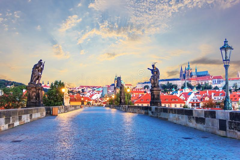 Статуи и взгляд Карлова моста на замке Праги на восходе солнца стоковая фотография rf