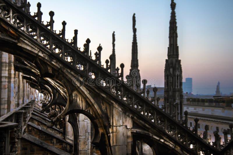 Статуи и декоративные элементы на крыше Duomo Милан вечера, взгляд города от террасы Duomo стоковое изображение rf
