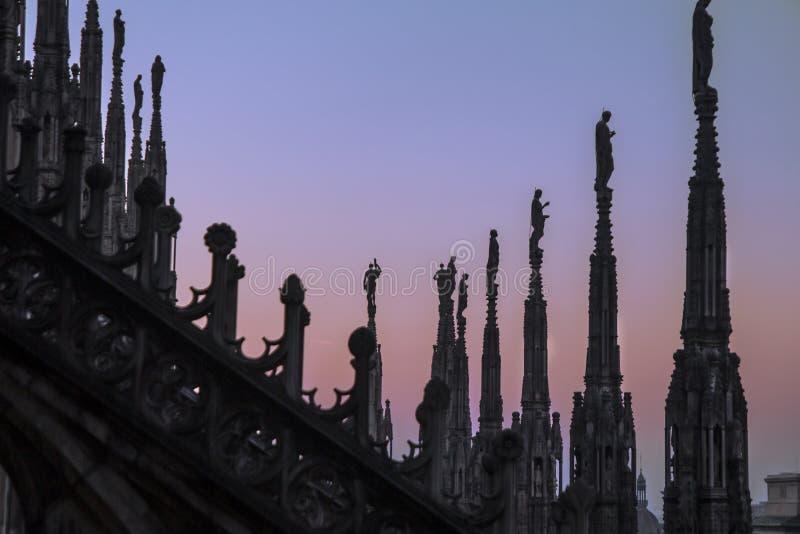 Статуи и декоративные элементы на крыше Duomo Милан вечера, взгляд города от террасы Duomo стоковые фото