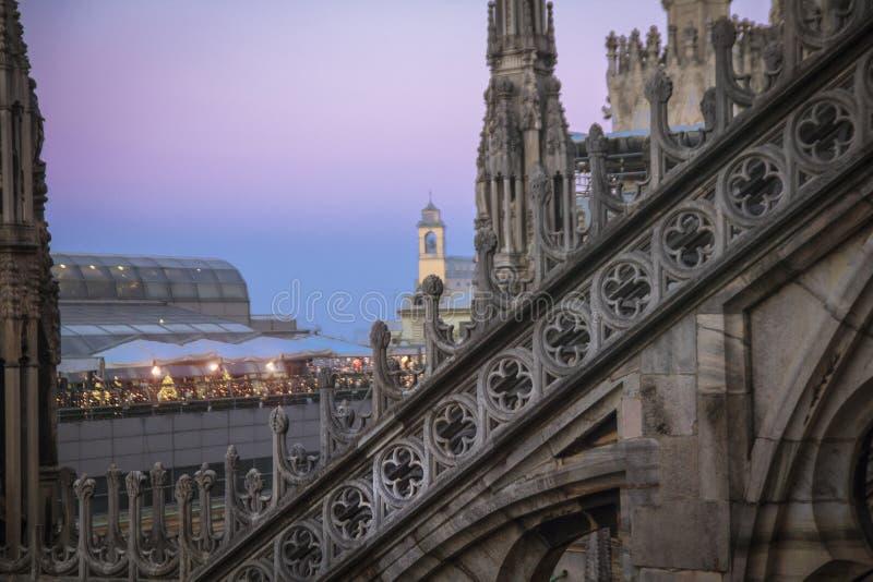 Статуи и декоративные элементы на крыше Duomo Милан вечера, взгляд города от террасы Duomo стоковая фотография