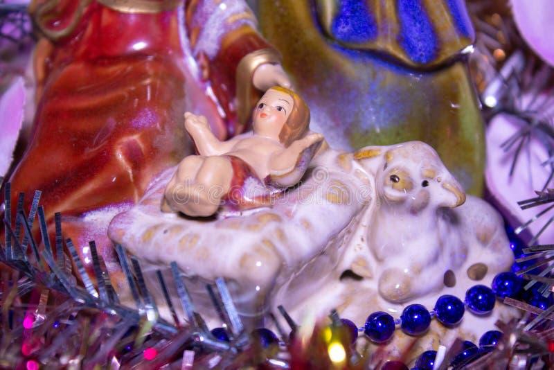 Статуэтт christmas jesus, закрытие маленького джеса в рождественской сцене с ягненком стоковое изображение rf