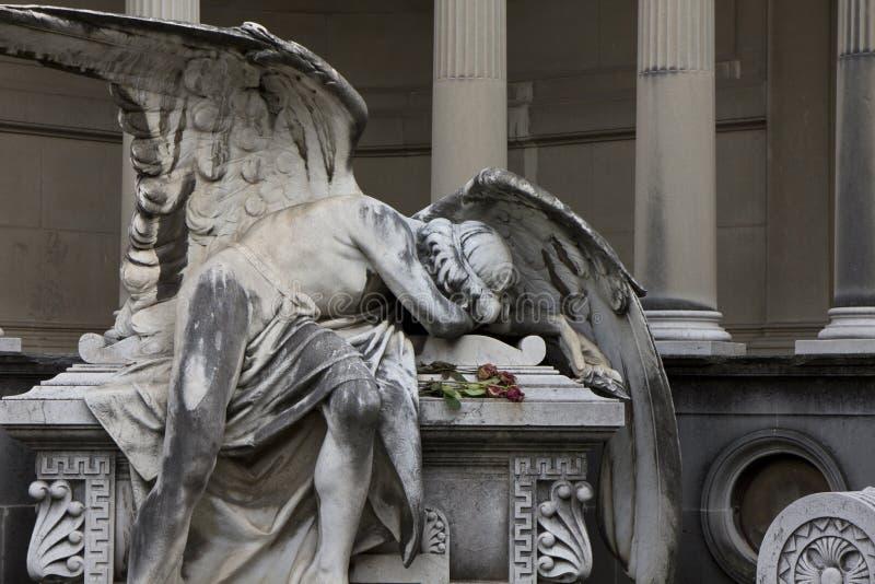 Статуя ангела лежа на усыпальнице жалея потеря быть стоковое изображение