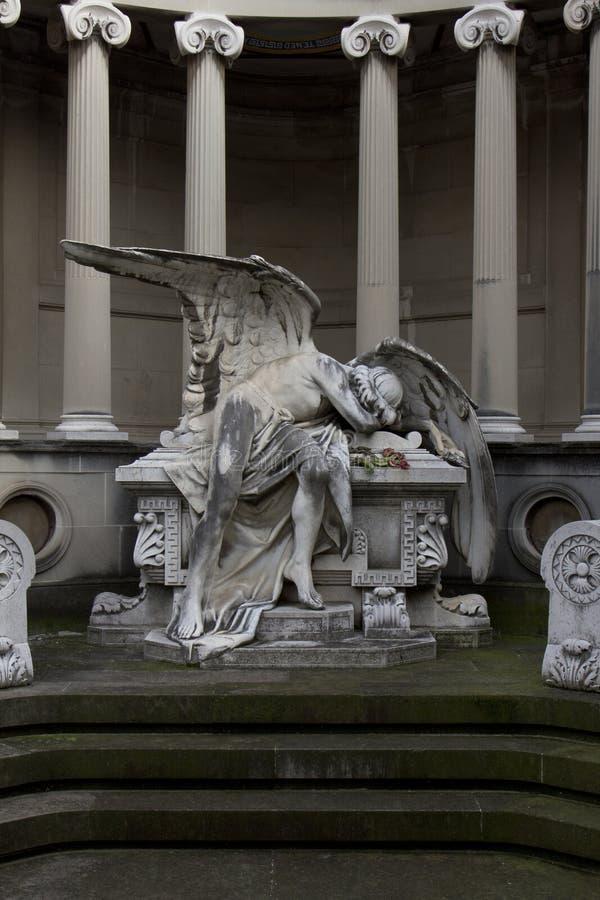 Статуя ангела лежа на усыпальнице жалея потеря стоковая фотография rf
