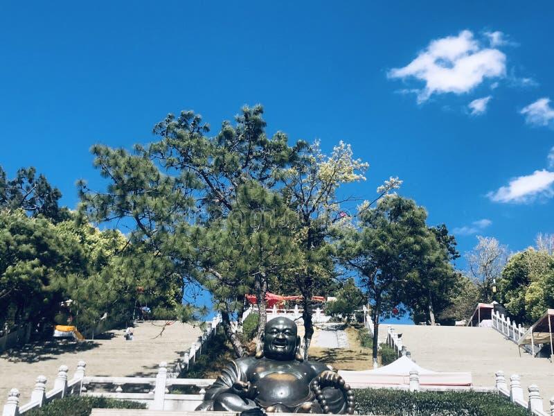 Статуя Будды, под голубым небом и белыми облаками стоковые фото