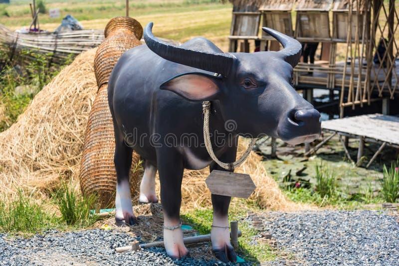статуя буффало возле рисового поля стоковое изображение