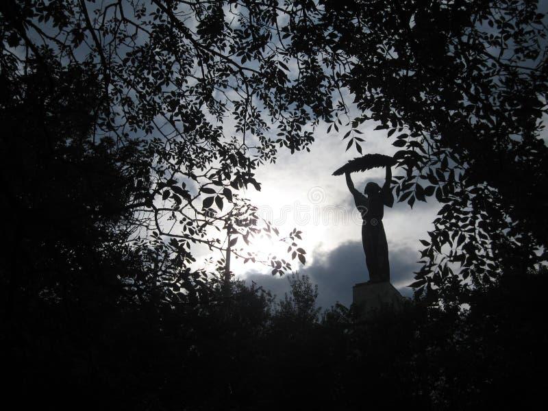 Статуя дамы держа лист среди листьев стоковое изображение