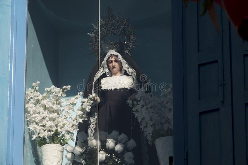 Статуя девственницы на окне с белыми цветками стоковое фото rf