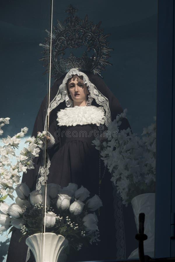 Статуя девственницы с белыми цветками на окне стоковое фото rf