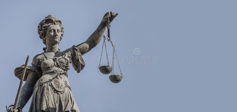 Статуя женщина судьи с масштабами и шпага на ровном голубом backgr стоковые фото