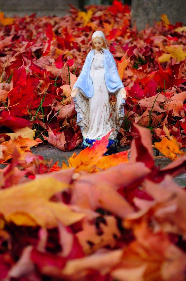 Статуя женщины в листьях падения стоковая фотография rf