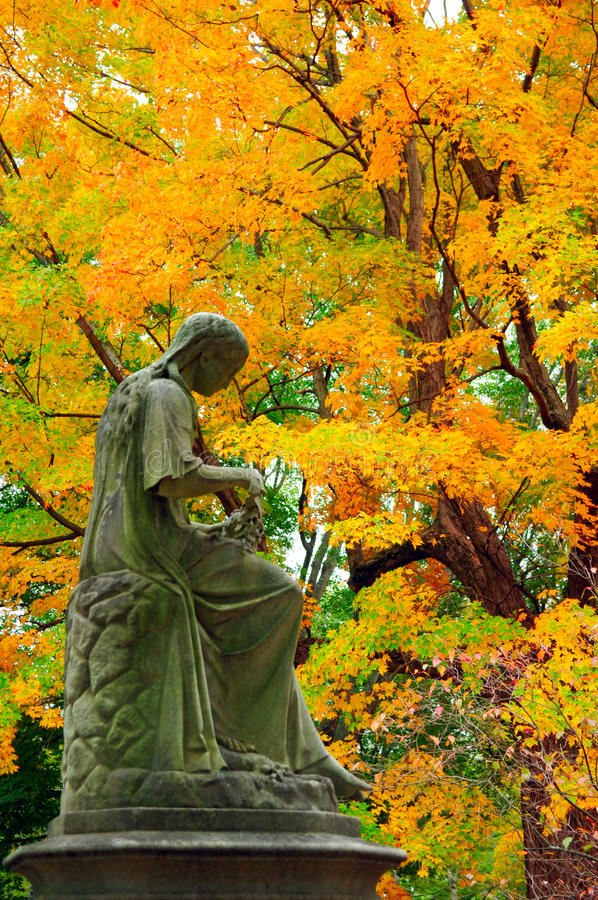 Статуя женщины в листьях падения стоковые фотографии rf