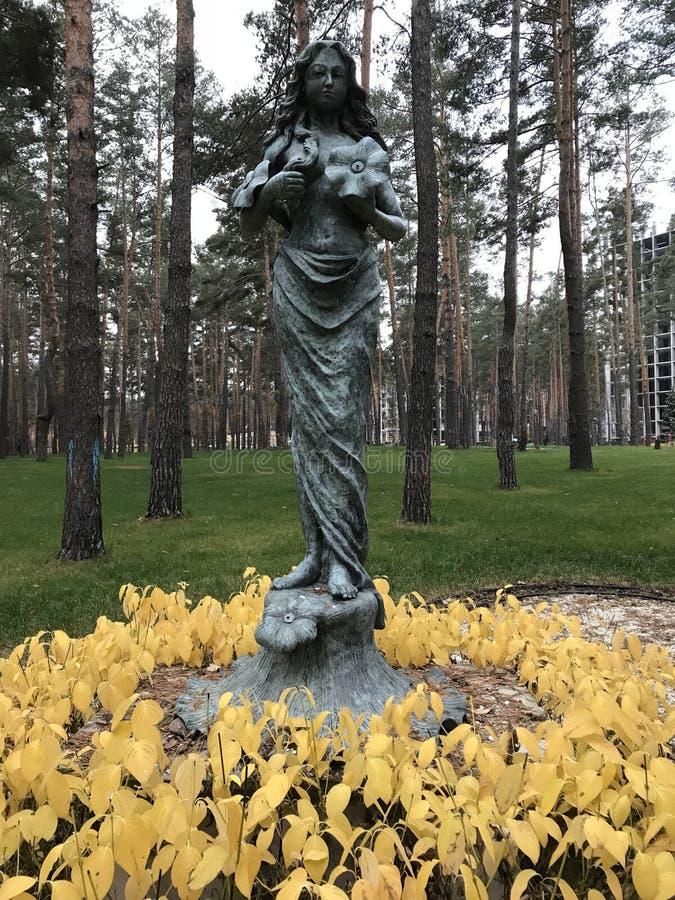 Статуя женщины держит цветок и стоит в кольце листовых золот стоковое изображение