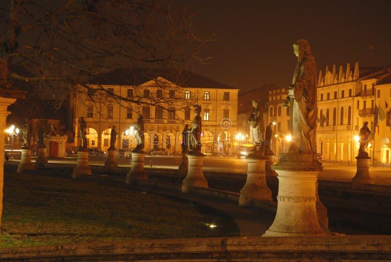 Статуя и здания в ноче стоковая фотография
