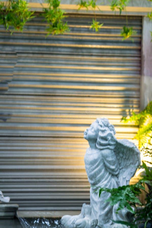 Статуя купидона в уютном саде стоковые фотографии rf