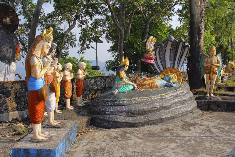 Статуя лорда Vishnu отдыхая на змейке Sheshnaag, с усаживанием Lakshmi жены и лордом Brahma, висок Nilkantheshwar стоковые изображения