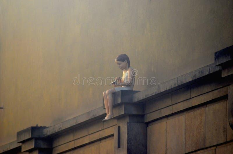 Статуя маленькой девочки сидя на стене стоковые изображения rf