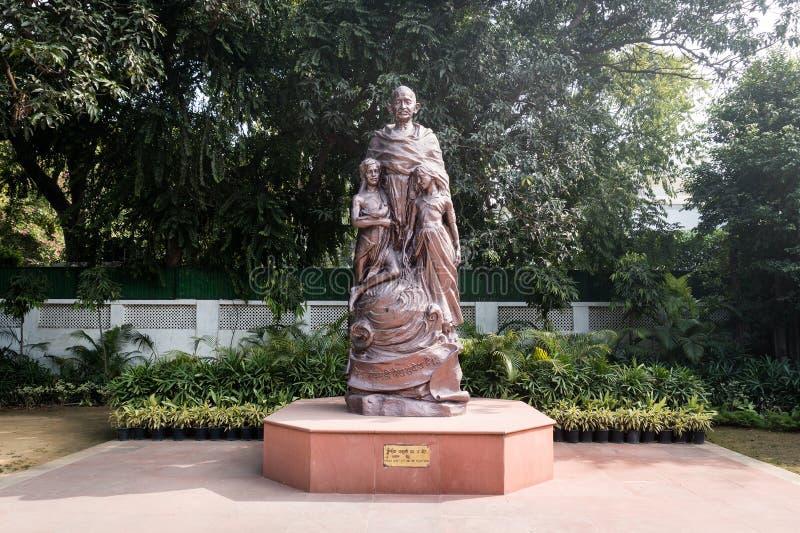 Статуя Махатма Ганди с детьми в бронзе стоя в дворе стоковая фотография rf