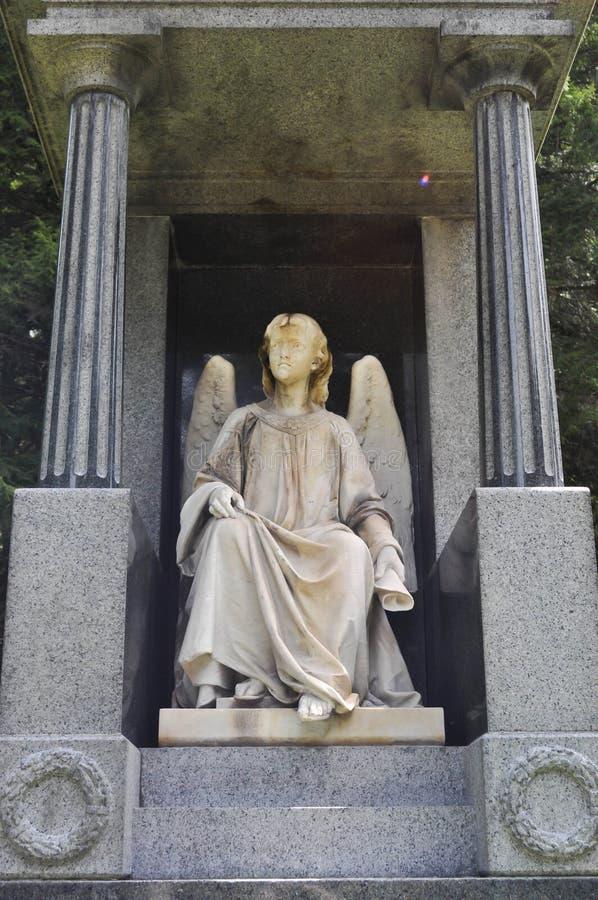 Статуя мраморного ангела сидя и смотря левая сторона в кладбище стоковое изображение