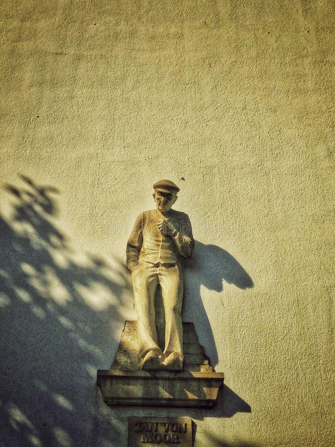 Статуя на стене в тенях стоковое изображение