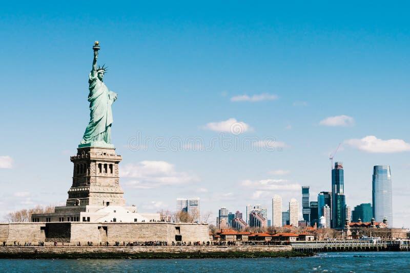 Статуя свободы на солнечный день с островом Нью-Йорка Манхэттена в предпосылке Символ нации городского пейзажа Америки, Соединенн стоковые изображения