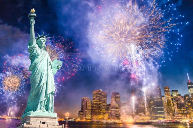 Статуя свободы с запачканной предпосылкой городского пейзажа с красивыми фейерверками на ноче, Манхаттаном, Нью-Йорком стоковая фотография rf