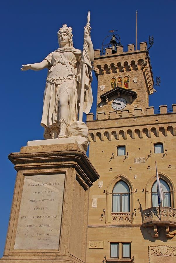 Статуя свободы с общественным дворцом на заднем плане на della Liberta аркады, Республике Сан-Марино стоковая фотография