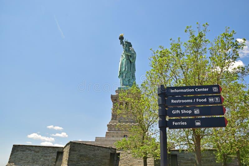 Статуя свободы с деревьями и направлением стоковое фото