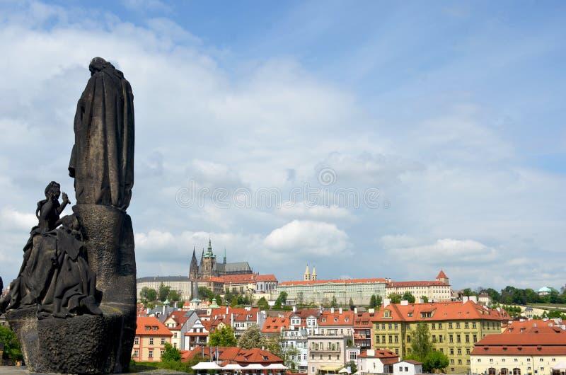 Статуя смотрит от Карлова моста к замку Праги стоковое изображение