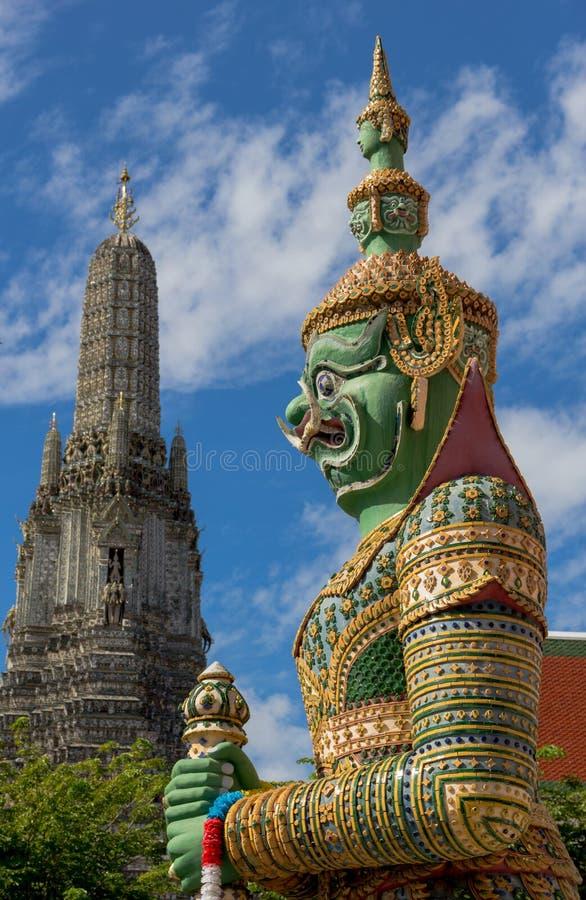 Статуя с предпосылкой Temple of Dawn, Таиланд радетеля стоковые изображения