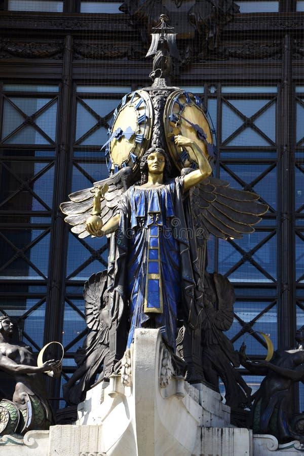 Статуя с часами на здании стоковое изображение rf