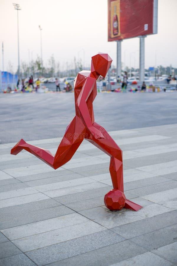 Статуя футболиста на вакантном поле вне залы спорт стоковая фотография rf