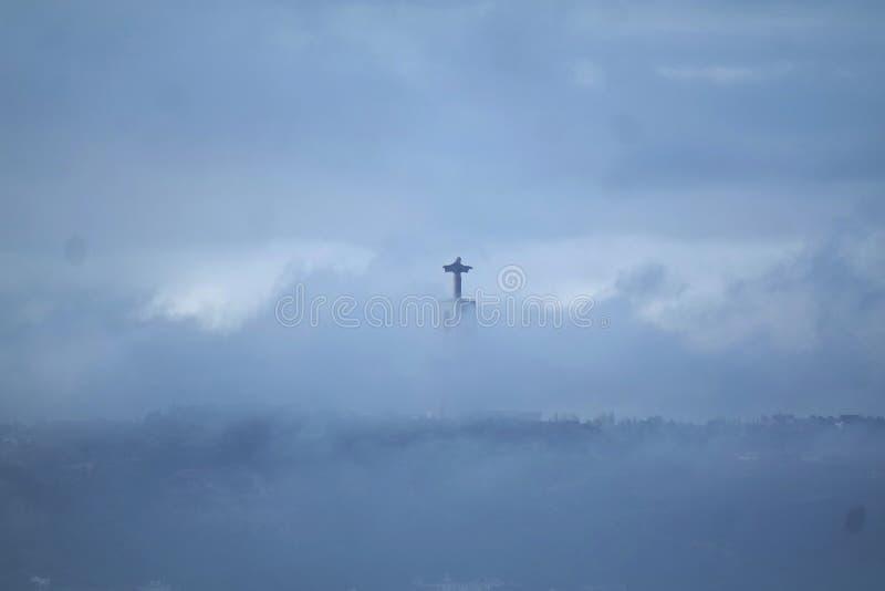 Статуя Христоса король в Лиссабоне через облака стоковые изображения