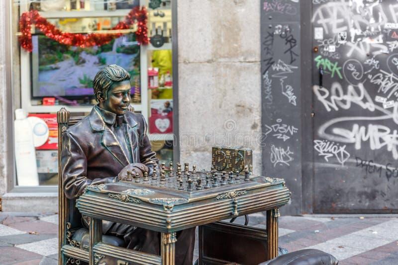 Статуя человека играет шахматиста, претендуя быть всей бронзой стоковая фотография rf