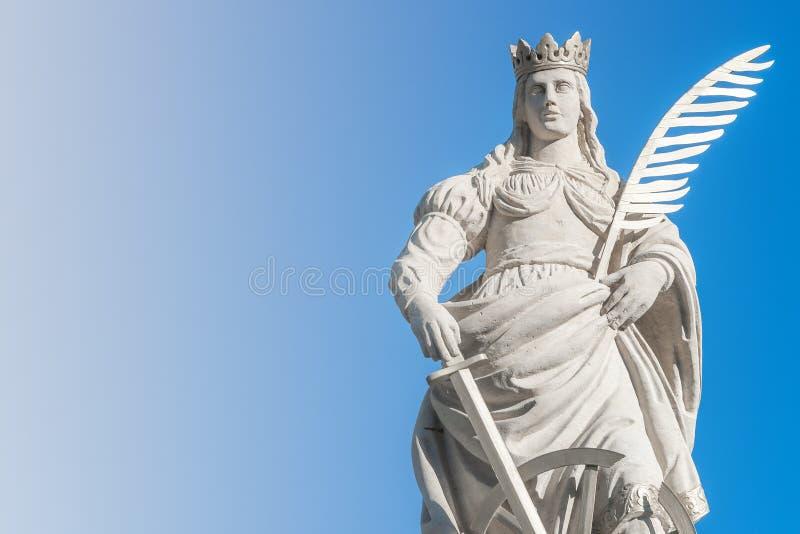 Статуя Catherin с записью пера птицы, шпаги и колеса телеги на старом портале в Магдебурге, Германии, крупном плане, сини градиен стоковое изображение rf