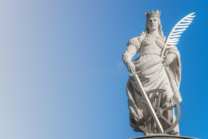 Статуя Catherin с записью пера птицы, шпаги и колеса телеги на старом портале в Магдебурге, Германии, крупном плане, сини градиен стоковые фотографии rf