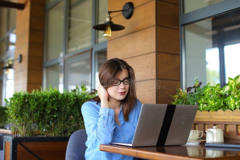Статья женского copywriter печатая компьтер-книжкой на ресторане стоковое фото rf