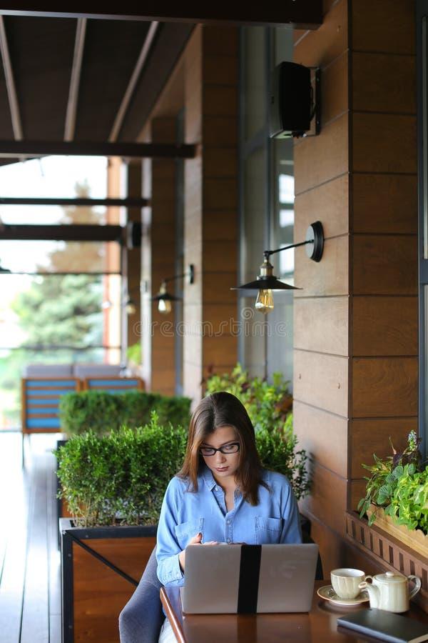 Статья женского copywriter печатая компьтер-книжкой на ресторане стоковые фото