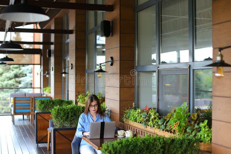 Статья женского copywriter печатая компьтер-книжкой на ресторане стоковые изображения