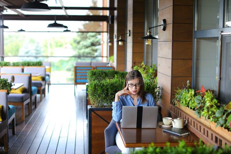Статья женского copywriter печатая компьтер-книжкой на ресторане стоковая фотография