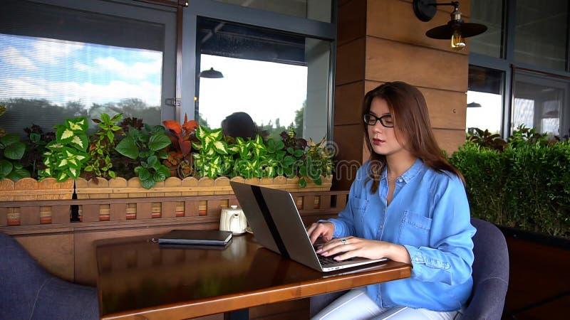 Статья женского copywriter печатая компьтер-книжкой на ресторане стоковое изображение rf