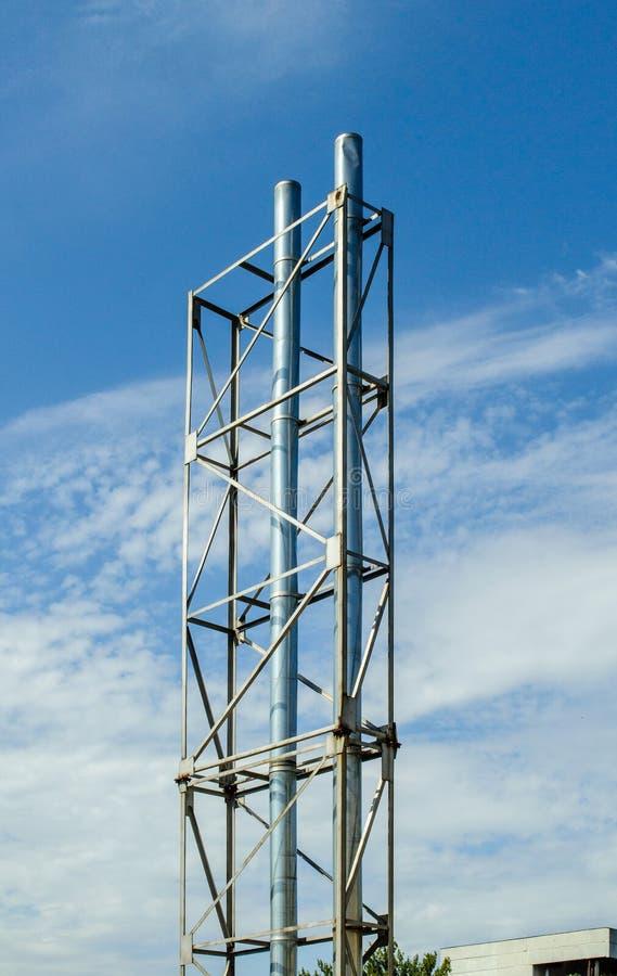 Стальные трубы против фабрики голубого неба стоковая фотография