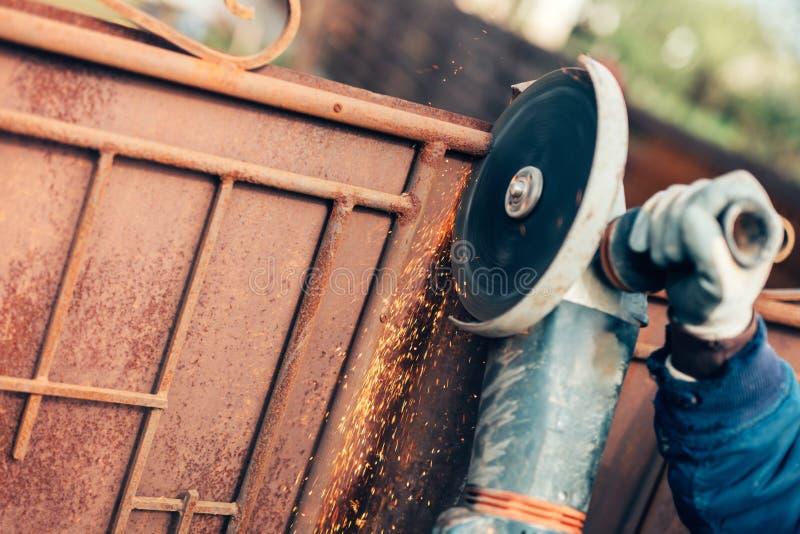 Сталь и металл вырезывания инженера по строительству и монтажу используя сверхмощную митру угла увидели и точильщик стоковое фото