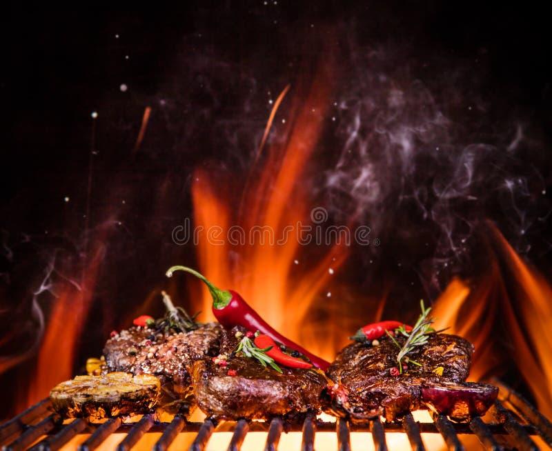 Стейки говядины на гриле с пламенами стоковые фотографии rf