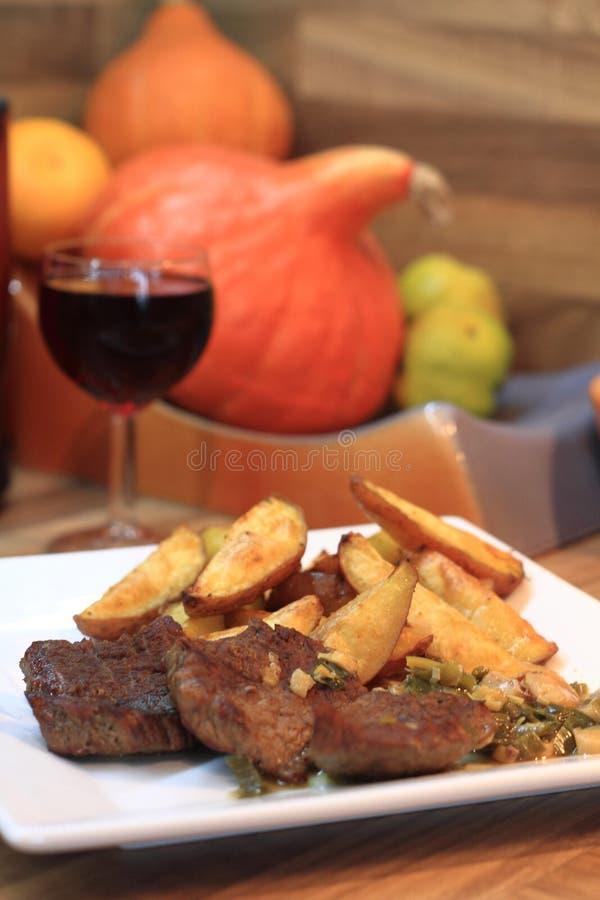 Стейки говядины с картошками и вином стоковая фотография rf
