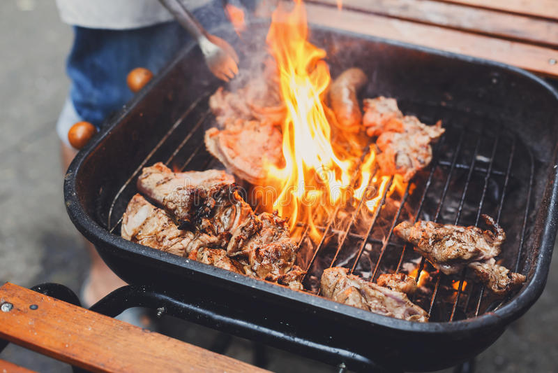Стейки гриля на металле скрежещут с пламенем, барбекю стоковая фотография